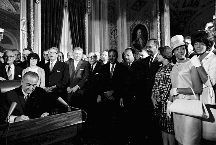 President_Lyndon_Johnson_signing_Voting_Rights_Act_with_Dr_Martin_Luthor_King_Jr_watching_Washington_DC_August_6_1965
